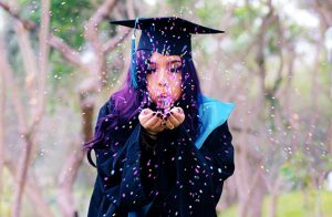 Girl in cap and gown blowing confetti