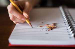 Someone writing in a notebook with pencil shavings on it