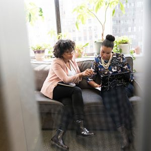 Two women in an office, looking at a laptop screen