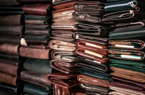 Multiple stacks of leather products, including wallets, books, and pouches