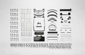 A typewriter that has been taken apart to show the various components that make up the product. All the pieces are laid out neatly.