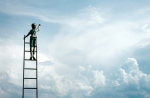 Against a background of clouds, a child is standing on a ladder reaching for the sky