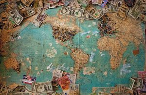 A world map, continents have push pins in them and different currencies around the boarder of the map