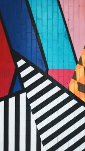 Geometric painting of various colors on a wall, including the colors red, blue, orange, and black