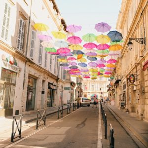 Different colored umbrellas suspended between city buildings over a one lane street.