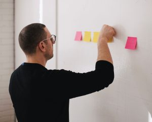 Man standing at white board putting up post it notes.