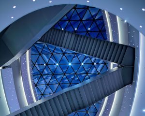 Looking up at a glass ceiling from inside the center of a geometrically complex designed blue building.