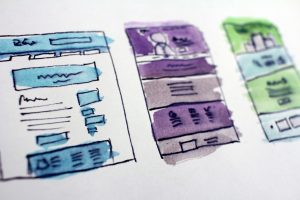 Website design layout on white paper with ink and color.