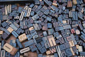 Scattered letter wood stamps.