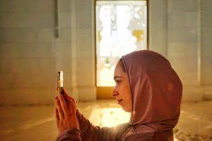Woman wearing hijab taking picture.