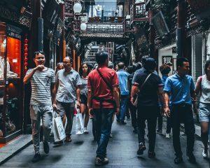 People walking on the street between buildings.