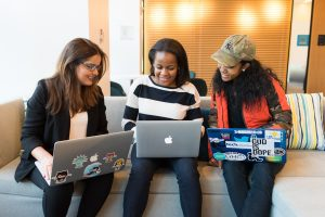 Three women sitting on a sofa using laptops.
