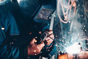 Man using welding machine while wearing a welding mask.