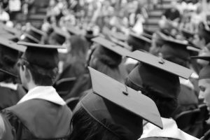 Black and white photo of large group of people wearing graduation caps with no visible faces.